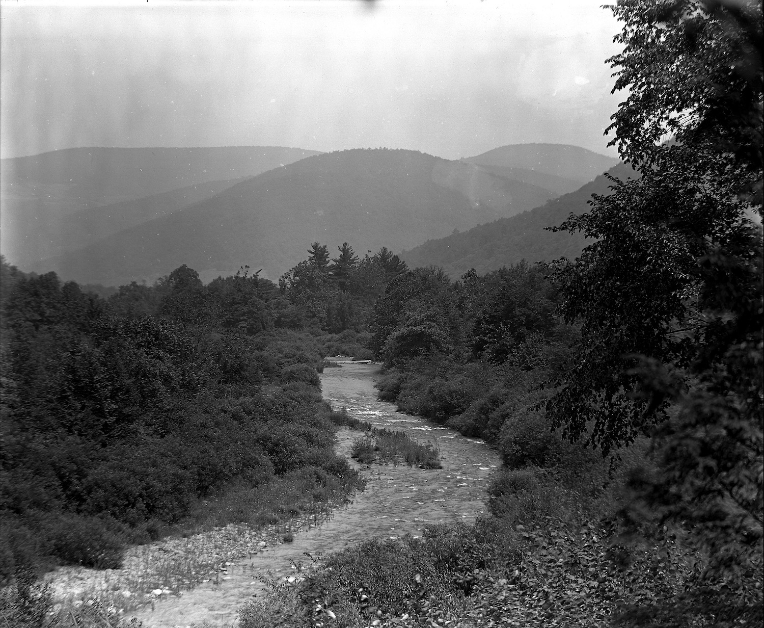 The Esopus Creek near Big Indian looking toward Rose Mountain, 1919. This image was taken for the New York State Conservation Committee in an effort to record Catskill forest-related activities.